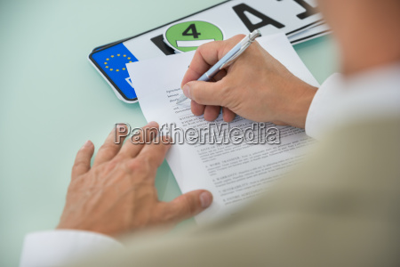 businessman filling car sale contract form