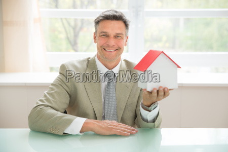 happy businessman holding house model