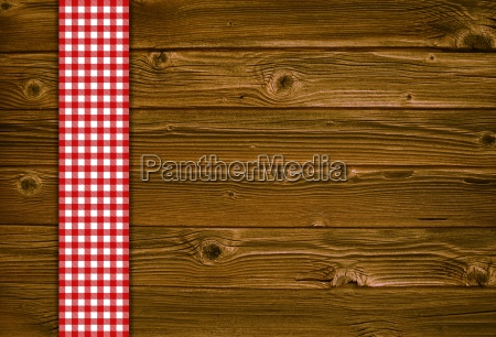 wooden background with red white tablecloth