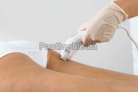 woman receiving laser treatment on buttock
