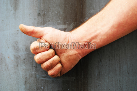 male right hand showing thumbs up