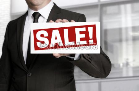businessman replies sale sign
