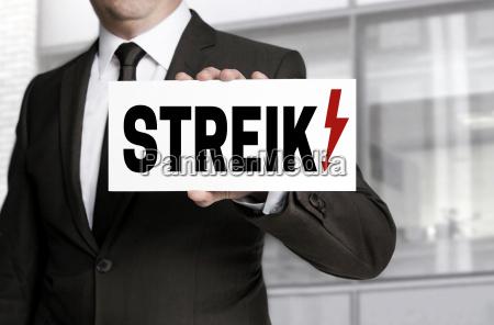 businessman holding strike against shield