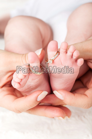 baby feet with wedding rings