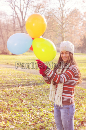 happy young woman with colorful balloons