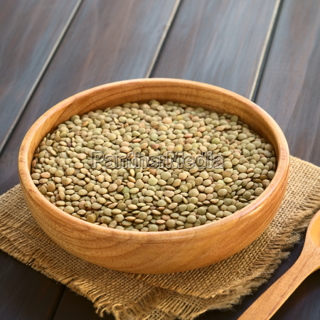 raw lentils in wooden bowl