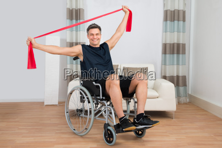 handicapped man on wheelchair exercising with