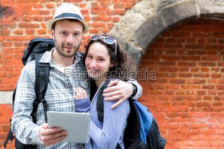 young couple of tourists using tablet