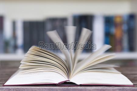 open book in front of bookshelf