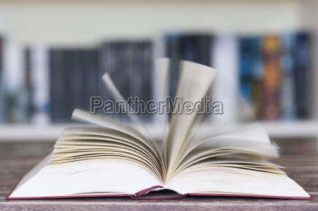 opened book in front of bookshelf