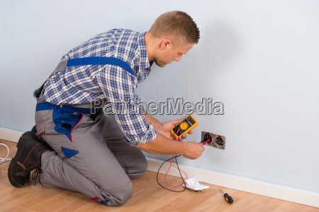 electrician checking voltage with multimeter