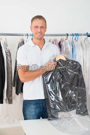 man holding coat in dry cleaning