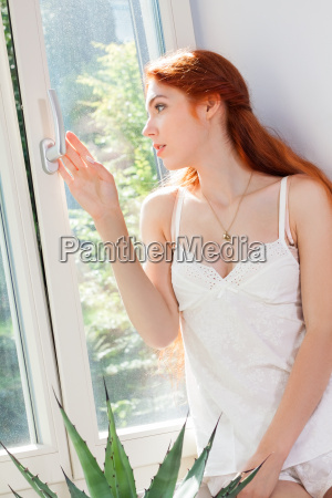 young woman sits in nightwear morning