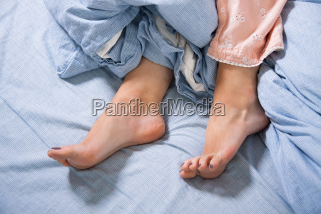 female feet with pajamas in bed