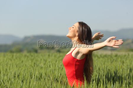 woman breathing deep fresh air in