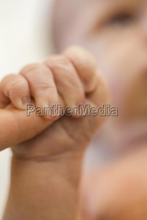 newborn baby grasps the finger of