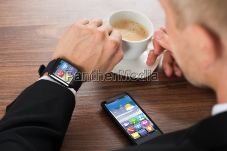businessman with smartphone and smartwatch drinking