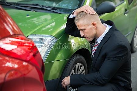 upset driver looking at car after