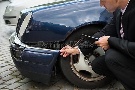 insurance expert examining car damage