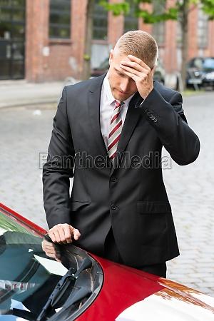 sad driver looking at parking ticket