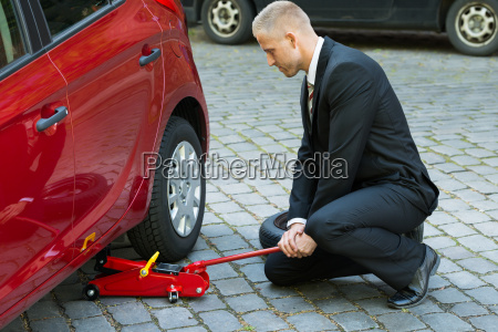 man using red hydraulic floor jack