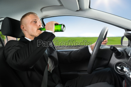 man drinks beer while driving car