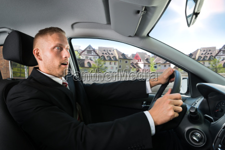 shocked businessman driving a car