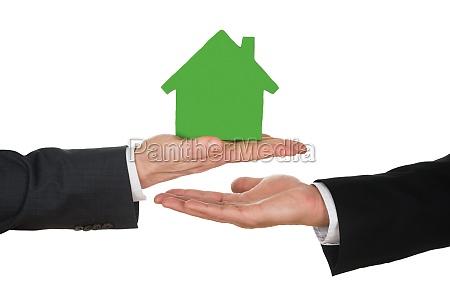 businessmans hand holding green house model