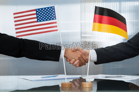 american and german businessman shaking hands