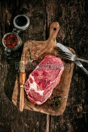 raw rib eye steak on wooden