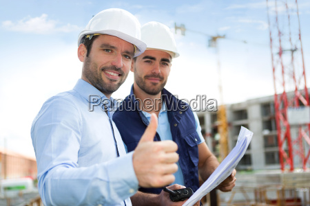 engineer and worker watching blueprint on