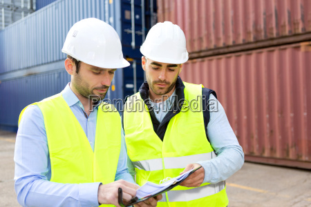 dock worker and supervisor checking containers