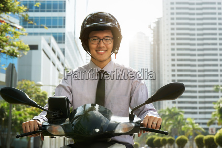 chinese businessman commuter using scooter motorcycle