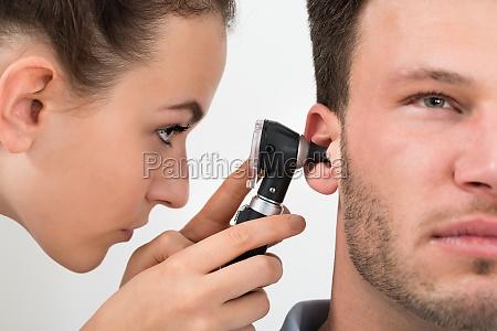 doctor examining mans ear