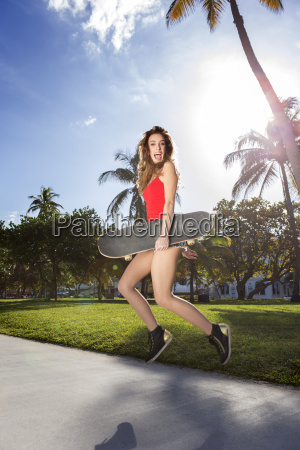 young woman jumping with a longboard