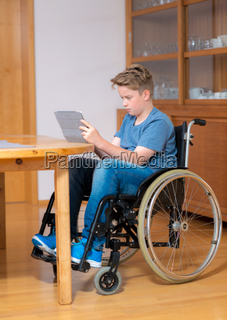 boy in wheelchair doing homework and
