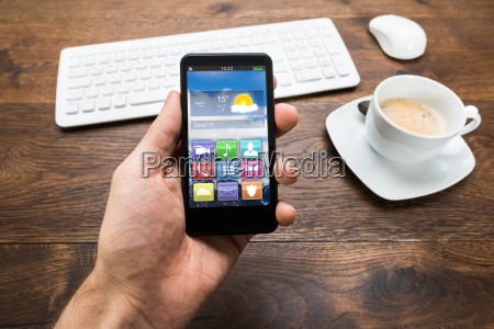 person holding mobile phone with tea
