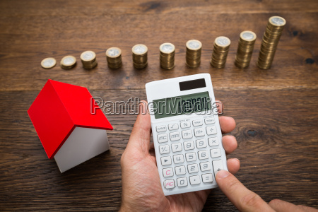 businessman with coins and house model