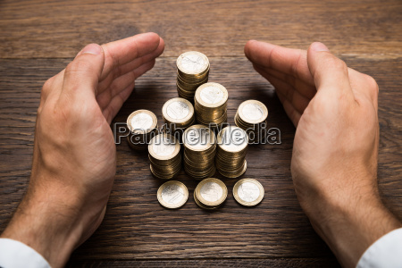 businessmans hand protecting euro coins