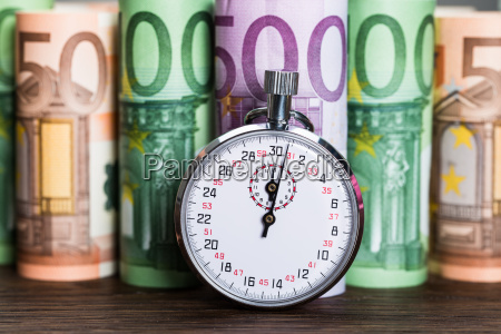 stopwatch in front of banknotes