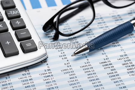 calculator with pen and eyeglasses on