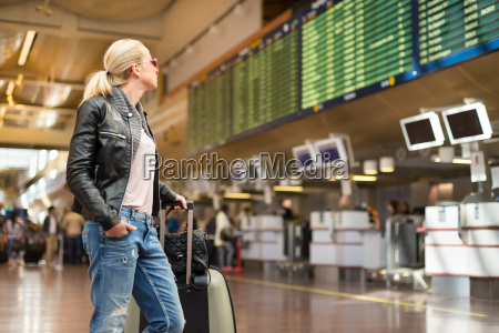 female traveller checking flight departures board