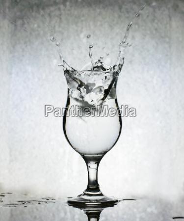 ice cubes splashing into glass of