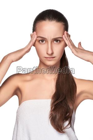 beautiful young woman with headache touching