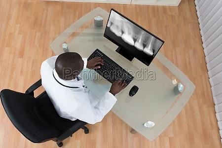 dentist analyzing x ray teeth on