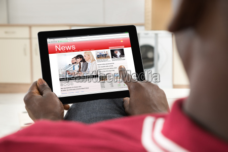 african man reading news on digital