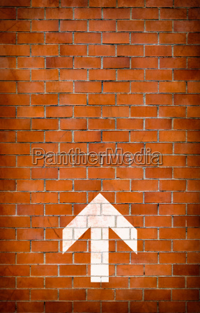 white arrow on brick wall