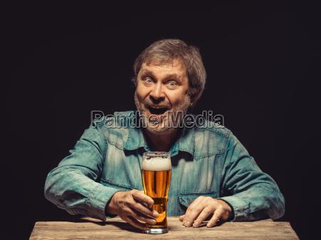 the smiling man in denim shirt