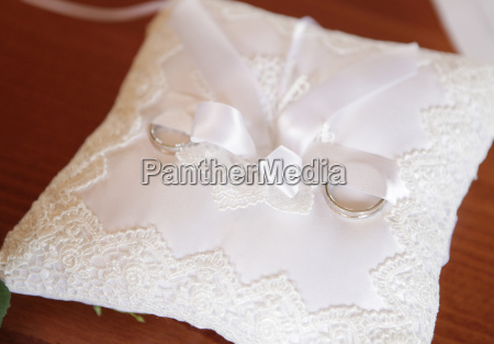 wedding rings on embroidered pillows