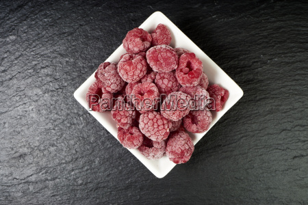 frozen raspberries in porcelain dish on